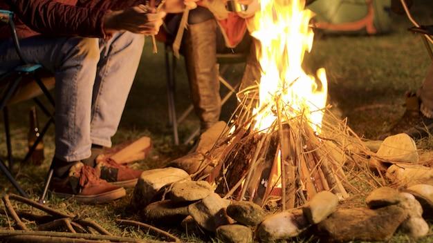 Imágenes de mano de un hombre haciendo una fogata para sus amigos en una noche fría.