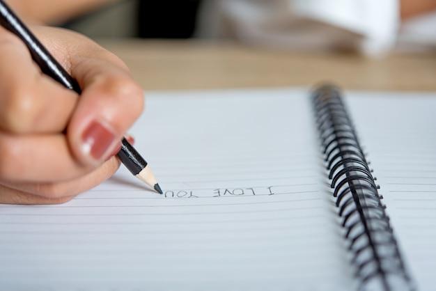 Imágenes de la mano y el lápiz de estudiantes que escriben el concepto de educación con espacio de copia