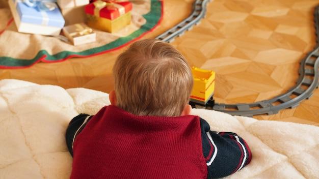 Imágenes de primer plano 4k de niño acostado en el piso y mirando el ferrocarril de juguete con tren del montar a caballo
