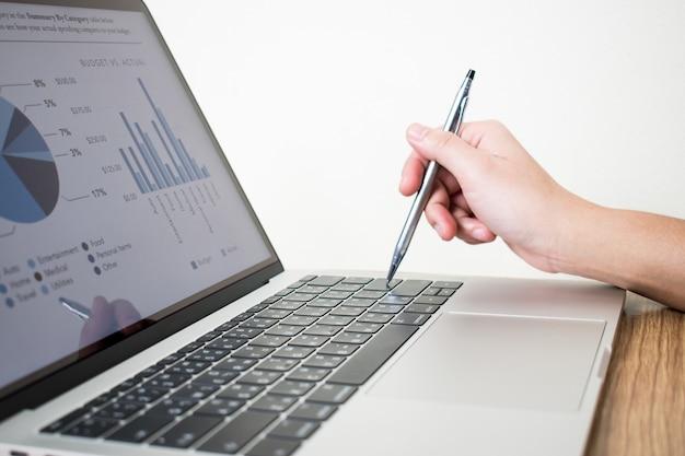 Imágenes de primer plano de hombres de negocios analizando datos de gráficos financieros en computadoras portátiles