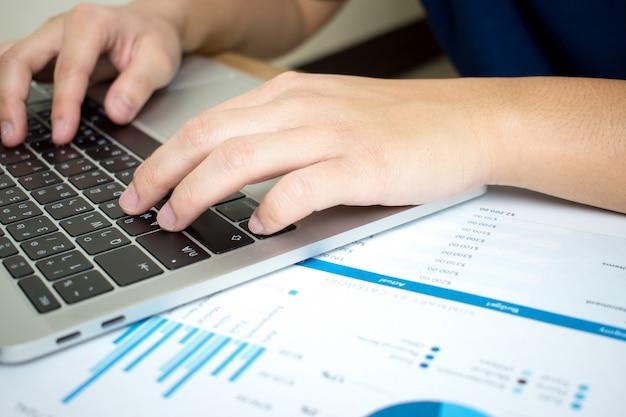 Imágenes de primer plano de hombres de negocios están analizando seriamente los gráficos financieros.