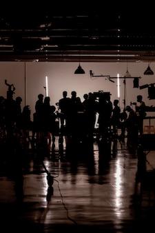 Imágenes de silueta de producción de video detrás de escena, equipo de luces y camarógrafo trabajando junto con el director en el estudio