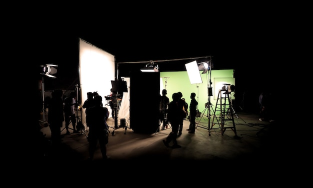 Imágenes de silueta de producción de video detrás de escena o b-roll o realización de película comercial de televisión que el equipo de filmación del equipo de iluminación y el camarógrafo trabajan junto con el director en el estudio con equipo