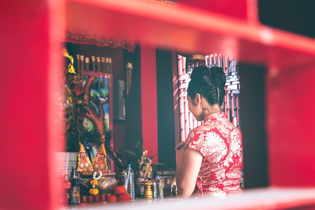 Imágenes suaves borrosas de una mujer asiática de pie en un santuario para respetar a los dioses
