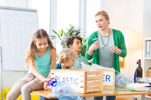 Importancia de la clasificación. útil maestra de escuela primaria que les cuenta a sus alumnos la importancia de la clasificación de residuos