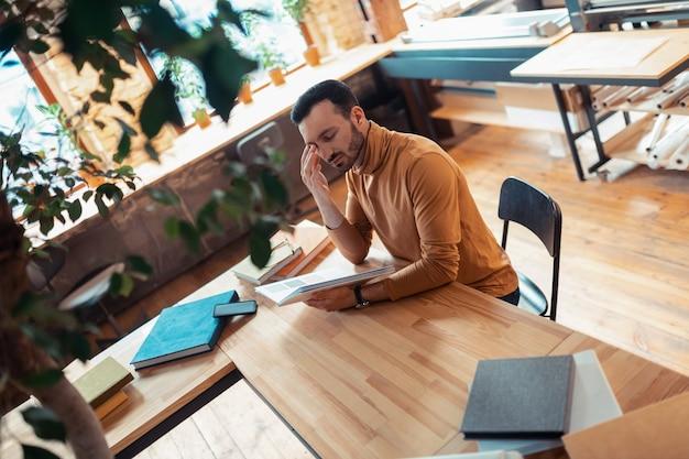 Imprenta. vista superior del guapo escritor sentado en la mesa trabajando en la imprenta