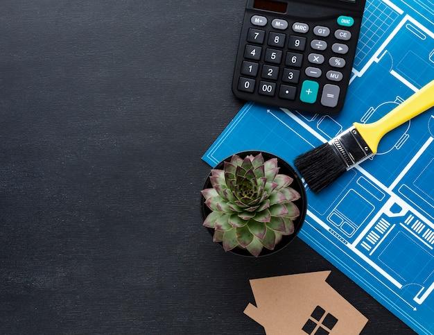 Impresión azul de una casa con planta suculenta y calculadora
