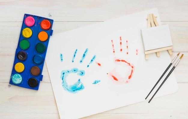 Impresión azul y roja de la mano en la hoja blanca con equipo de pintura sobre superficie de madera