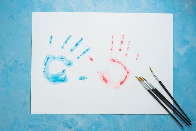 Impresión azul y roja de la mano en la hoja blanca con el pincel sobre fondo azul