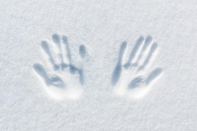 Impresión de dos manos sobre la nieve.