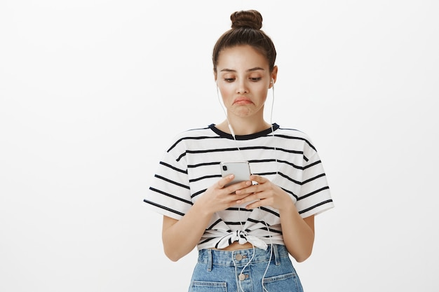 Impresionada chica atractiva y elegante satisfecha con no está mal podcast o video, mirando el teléfono inteligente en auriculares