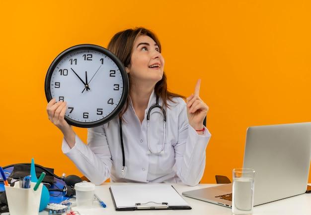 Impresionada doctora de mediana edad con bata médica y un estetoscopio sentado en el escritorio con portapapeles de herramientas médicas y una computadora portátil con reloj mirando al lado apuntando hacia arriba