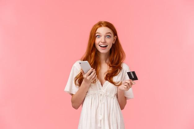 Impresionada y emocionada, feliz niña pelirroja con vestido blanco, sorprendida de lo fácil que hizo la compra