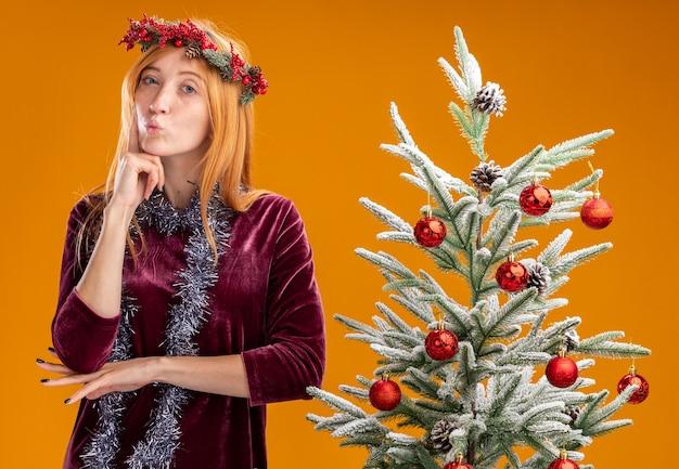 Impresionada frunciendo los labios joven hermosa niña de pie cerca del árbol de navidad con vestido rojo y corona con guirnalda en el cuello poniendo el dedo en la mejilla aislado en la pared naranja