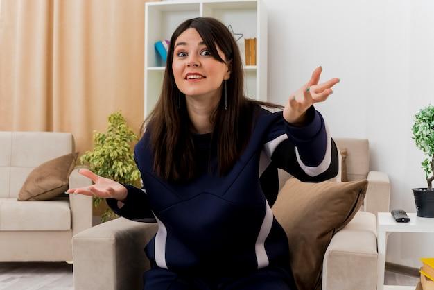 Impresionada joven bastante caucásica sentada en un sillón en la sala de estar diseñada mostrando las manos vacías mirando