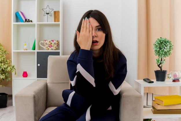 Impresionada joven bonita mujer caucásica sentada en un sillón en la sala de estar diseñada poniendo la mano en la cara que cubre la mitad de la cara mirando