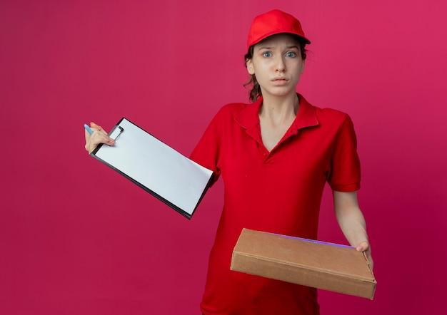 Impresionada joven bonita repartidora en uniforme rojo y gorra con bolígrafo de paquete de pizza y portapapeles aislado sobre fondo carmesí
