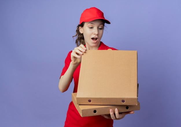 Impresionada joven bonita repartidora vestida con uniforme rojo y gorra sosteniendo paquetes de pizza y mirando dentro del paquete aislado sobre fondo púrpura con espacio de copia