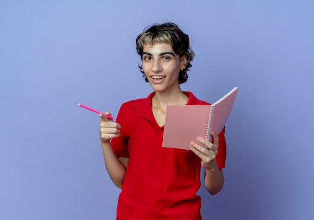 Impresionada joven caucásica con corte de pelo pixie sosteniendo bloc de notas y bolígrafo y apuntando a la cámara con el dedo aislado sobre fondo púrpura con espacio de copia