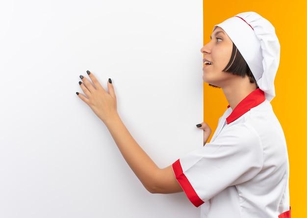 Impresionada joven cocinera en uniforme de chef de pie cerca de la pared blanca sosteniendo y poniendo la mano y mirándolo aislado en naranja con espacio de copia