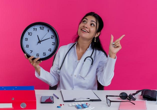 Impresionada joven doctora vistiendo bata médica y estetoscopio sentado en el escritorio con herramientas médicas sosteniendo el reloj girando de cabeza a lado mirando hacia arriba y levantando el dedo aislado en la pared rosa