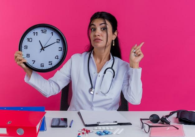 Impresionada joven doctora vistiendo bata médica y estetoscopio sentado en el escritorio con herramientas médicas sosteniendo el reloj y levantando el dedo aislado en la pared rosa