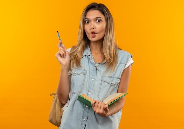 Impresionada joven estudiante bonita con bolsa trasera sosteniendo libro abierto y bolígrafo aislado en naranja
