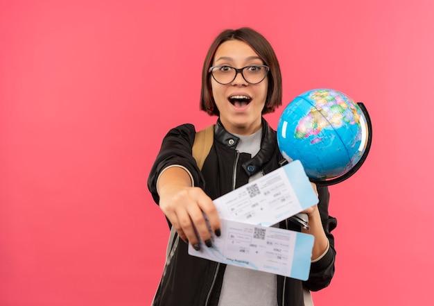 Impresionada joven estudiante con gafas y bolsa trasera estirando boletos de avión y sosteniendo globo aislado en rosa