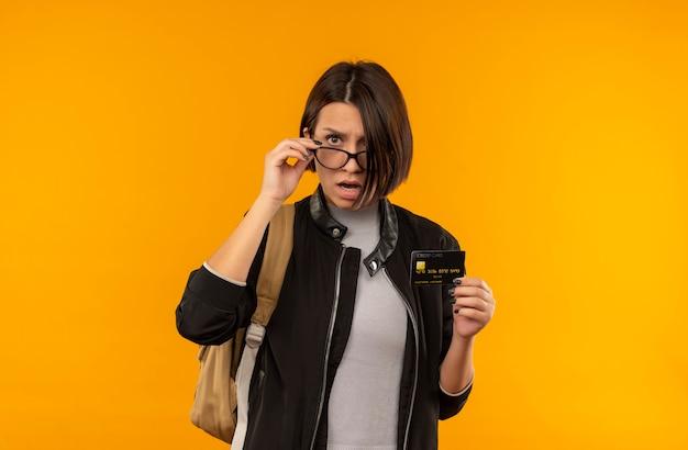 Impresionada joven estudiante con gafas y bolsa trasera con tarjeta de crédito poniendo la mano en vasos aislados en naranja