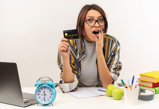 Impresionada joven estudiante con gafas sentado en el escritorio con tarjeta de crédito y poner la mano en el mentón aislado en blanco
