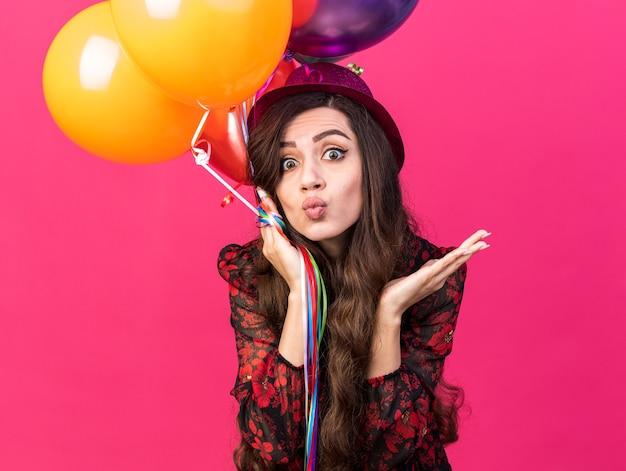 Impresionada joven fiestera con gorro de fiesta sosteniendo globos haciendo gesto de beso mostrando la mano vacía aislada en la pared rosa