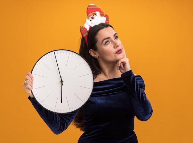 Impresionada joven hermosa vestida con un vestido azul y un aro de pelo de navidad sosteniendo el reloj de pared poniendo la mano en la mejilla aislada sobre fondo naranja