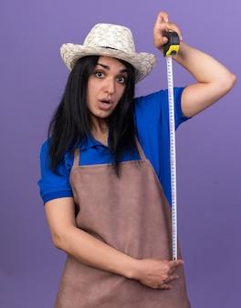 Impresionada joven jardinero mujer vestida con uniforme y sombrero sosteniendo medidor de cinta mirando al frente aislado en la pared púrpura