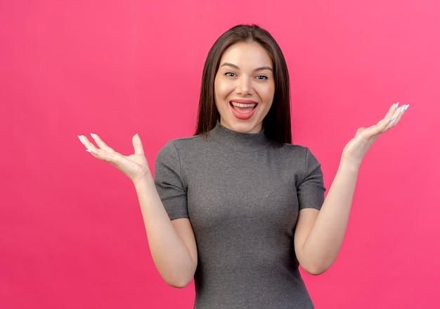 Impresionada joven mujer bonita mostrando las manos vacías aisladas sobre fondo rosa