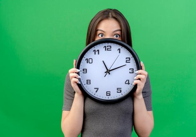 Impresionada joven mujer bonita sosteniendo el reloj y mirando directamente desde atrás aislado sobre fondo verde con espacio de copia