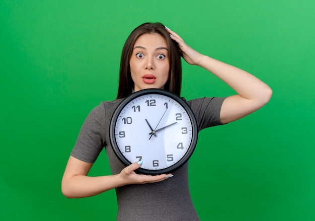 Impresionada joven mujer bonita sosteniendo el reloj y poniendo la mano en la cabeza aislada sobre fondo verde