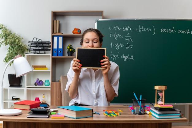 Impresionada joven profesora de matemáticas sentada en un escritorio con útiles escolares sosteniendo una mini pizarra delante de la boca mirándola en el aula