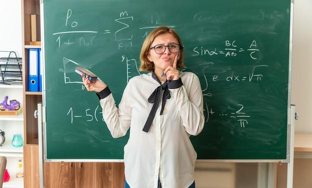 Impresionada joven profesora de pie delante de las herramientas de pizarra sosteniendo el tablero de esponja en el aula