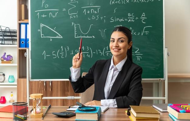 Impresionada joven profesora se sienta a la mesa con herramientas escolares levantando la pluma en el aula