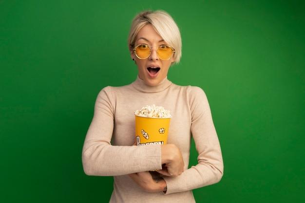 Impresionada joven rubia abrazando el cubo de palomitas de maíz