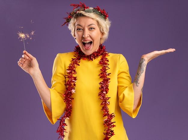 Impresionada joven rubia con corona de navidad y guirnalda de oropel alrededor del cuello sosteniendo bengala de vacaciones mirando a cámara mostrando la mano vacía aislada sobre fondo púrpura