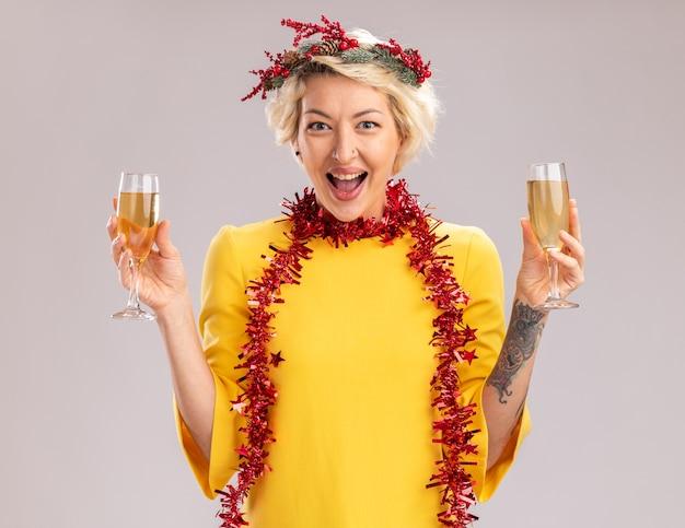 Impresionada joven rubia con corona de navidad y guirnalda de oropel alrededor del cuello sosteniendo dos copas de champán mirando a cámara aislada sobre fondo blanco