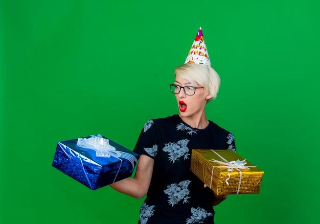 Impresionada joven rubia fiestera con gafas y gorro de cumpleaños sosteniendo cajas de regalo mirando uno de ellos aislado sobre fondo verde