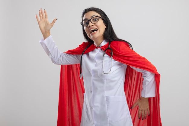 Impresionada joven supermujer con gafas y un estetoscopio mirando al frente haciendo baile robot aislado en la pared blanca