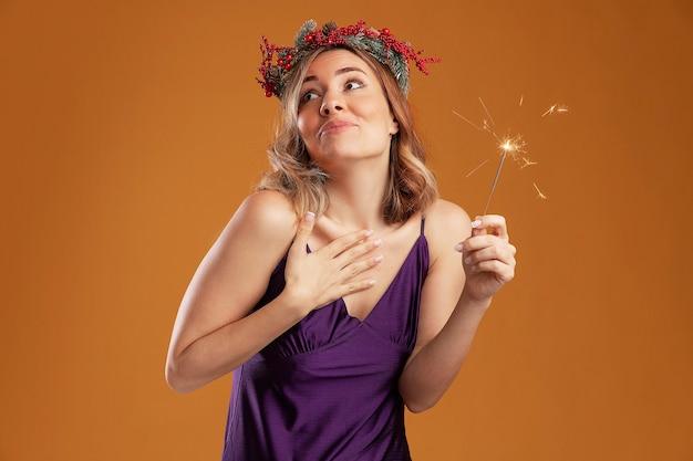 Impresionada mirando lado hermosa joven vestida de púrpura con corona con luces de bengala poniendo la mano a sí misma aislada sobre fondo marrón