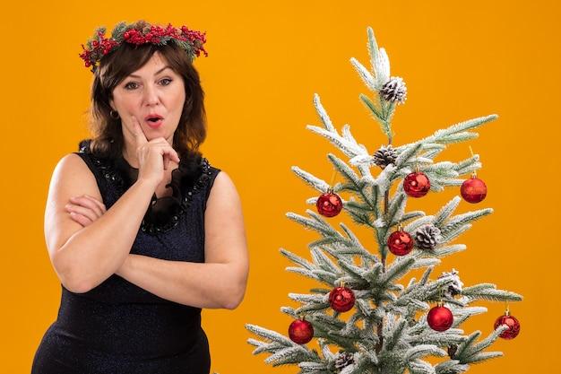 Impresionada mujer de mediana edad vistiendo corona de navidad y guirnalda de oropel alrededor del cuello de pie cerca del árbol de navidad decorado