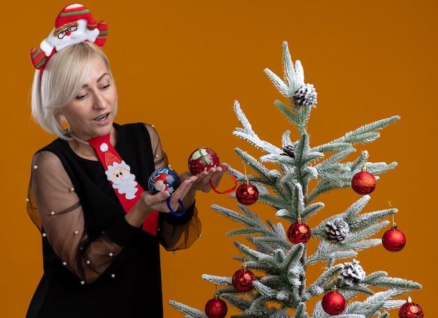 Impresionada mujer rubia de mediana edad con diadema de santa claus y corbata de pie cerca del árbol de navidad decorado sosteniendo y mirando adornos navideños aislados sobre fondo naranja