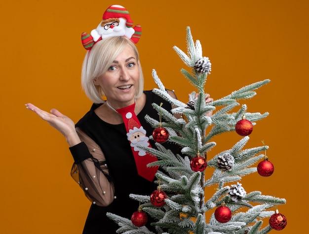 Impresionada mujer rubia de mediana edad con diadema de santa claus y corbata de pie detrás del árbol de navidad decorado tocándolo mirando a cámara mostrando la mano vacía aislada sobre fondo naranja