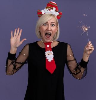 Impresionada mujer rubia de mediana edad con diadema de santa claus y corbata sosteniendo bengala de vacaciones mirando a cámara mostrando cinco con la mano aislada sobre fondo púrpura
