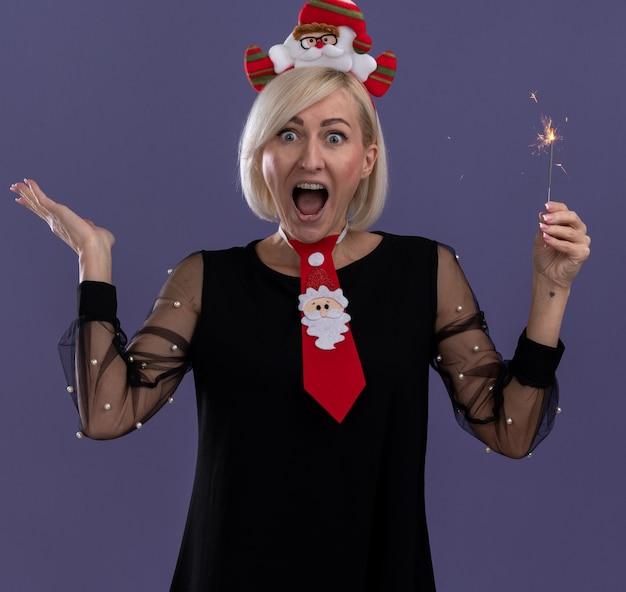 Impresionada mujer rubia de mediana edad con diadema de santa claus y corbata sosteniendo bengala de vacaciones mirando a cámara mostrando la mano vacía aislada sobre fondo púrpura